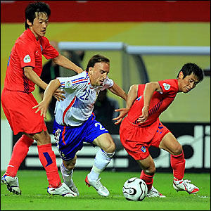 Franck Ribery (centre) goes between South Korean midfielders Kim Nam-il (left) and Baek Ji-hoon