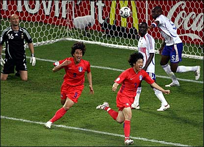 France defender William Gallas (right) kicks the ball in anger as South Korean duo Park Ji Sung (centre) and Ahn Jung Hwan  celebrate