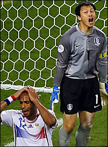 South Korea keeper Lee Woon-Jae (right) reacts after saving from Thierry Henry (left)