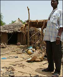 Man stands in remains of Djawara village