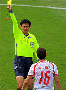 Singapore referee Shamsul Maidin shows a yellow card to Arkadiusz Radomski