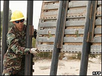A construction worker with the Utah National Guard helps build a wall along the border with Mexico