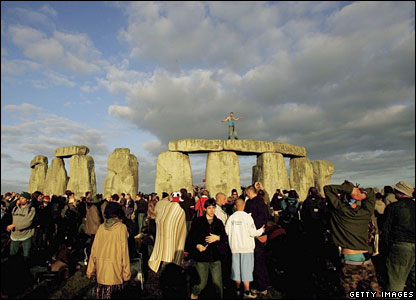 A man stands on top of Stonehenge as the sun rises