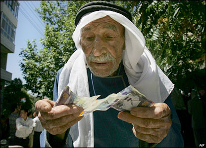 A Palestinian government employee counts his money in Ramallah