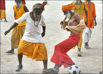 Hindu ascetics play football on the banks of the River Ganges