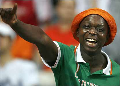 An Ivory Coast fan cheers on his side