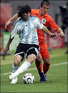 Argentina's Lionel Messi holds off Holland's Rafael Van Der Vaart