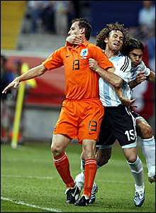Argentina defender Gabriel Milito (centre) gets to grips with Andre Ooijer (left)
