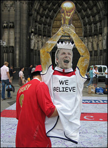 A fan holds a David Beckham statue in Cologne
