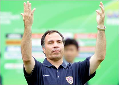 Coach Bruce Arena holds his hands up to the sky