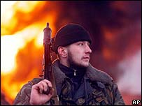 Russian soldier standing in front of a burning Chechen oil refinery