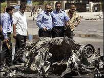 Iraqi men inspect the area where a car bomb exploded in Baghdad (Photo: Karim Sahib/AFP/Getty Image)