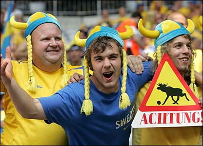 Three Sweden fans hold a warning sign