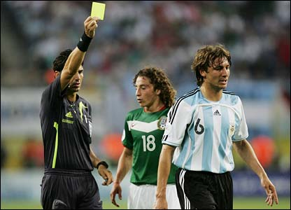 Referee Massimo Busacca awards a yellow card