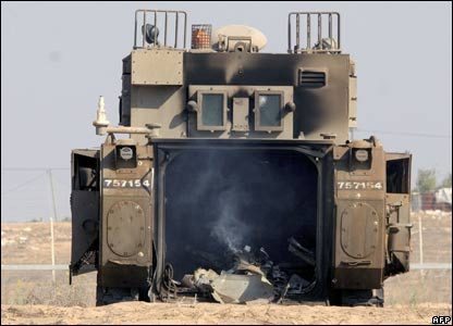 An Israeli armoured vehicle smoulders after an attack by Palestinian militants near the Gaza Strip.