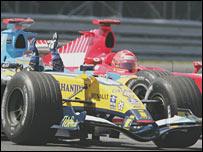 Fernando Alonso celebrates as he crosses the line ahead of Michael Schumacher