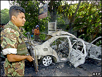 Bomb disposal squad officers stands near the wreckage of army major general Parami Kulatunga's car
