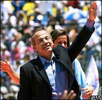 Candidate Felipe Calderon greets supporters from a stage in Mexico City's Azteca Stadium