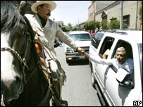 Candidate Andres Manuel Lopez Obrador shakes hands with a man dressed as Pancho Villa  in Durango