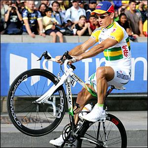 Robbie McEwen peforms a wheelie during the race