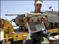 Israeli soldier reading about missing comrade, as a tank is transported towards Gaza