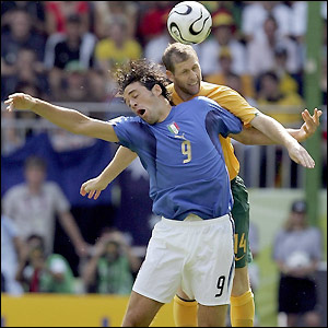 Luca Toni of Italy is challenged by Scott Chipperfield