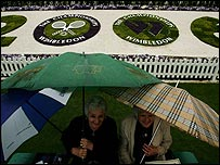 Fans shelter from the rain