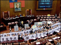 Taiwanese opposition legislators display banners that read 'Shame on Chen's supporters' before trying to pass a motion for a referendum to recall President Chen Shui-bian, Tuesday, June 27, 2006