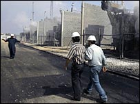 Palestinian workers inspect their damaged power station