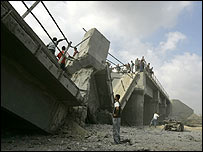 Palestinians look at a Gaza road bridge destroyed by Israeli bombers