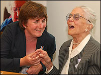 Photo of an older deafblind lady sharing a joke with a younger women