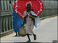Girl carrying her sister and belongings