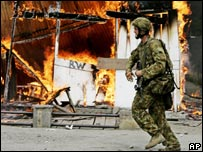 Australian solider goes past a burning building in Dili