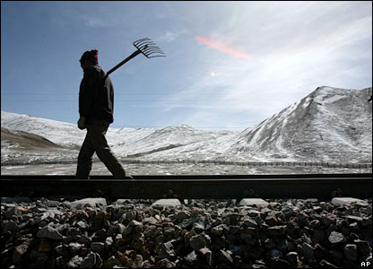 A worker walks along the railway line of the Qinghai-Tibet Railway in the Tanggula mountains, in Tibet, China, Friday May 5 2006