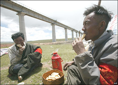Tibetan villagers eat lunch below the Qinghai-Tibet Railway line during a break while patrolling along the line -27/6/06