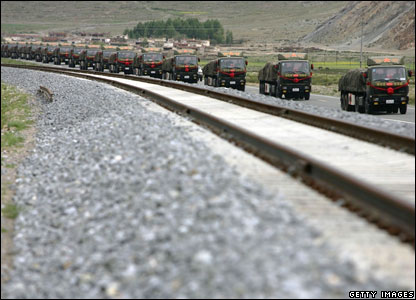 Chinese army trucks carry goods next to the Qinghai-Tibet Railway on June 25, 2006