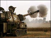 An Israeli mobile artillery unit fires a shell into the Gaza Strip