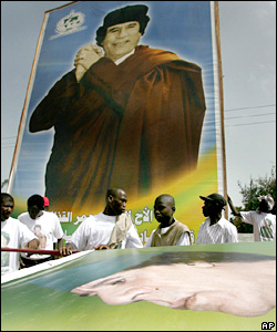 Workers put up posters of Libyan leader Muammar Gaddafi