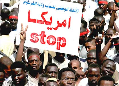 "Sudanese protesters hold up a banner in Arabic reading, ""America stop"", during a rally against UN plans to deploy peacekeepers to Darfur"