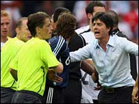 Slovakian referee Lubos Michel of Slovakia (L) and German assistant coach Joachim Loew (2nd R) try to help separate players