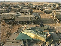 Israeli soldiers and tanks massed at the Gaza border on Friday