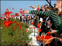 Mourners scattering poppies at the Somme memorial in northern France