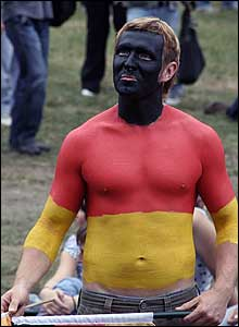 A German fan covered in body paint showing his flags colours