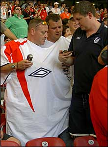 Two England fans share a double-person replica shirt