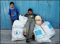 Children rest on sacks of grain in Gaza