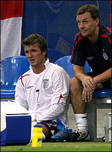 David Beckham sits on the floor by the England subsitute's bench