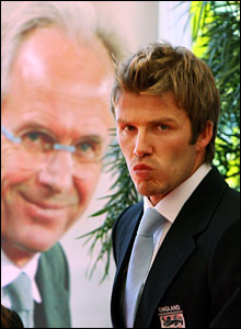 David Beckham walks past a poster of departing coach Sven-Goran Eriksson