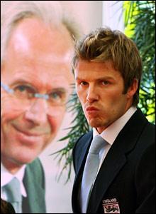 David Beckham walks past a poster of departing coach Sven-Goran Eriksson