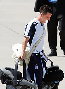 John Terry carries baby seats on to the plane