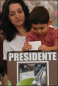Madre sostiene a hijo para depositar su voto.